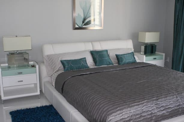 a mid-sized contemporary bedroom with cloud gray wall and teal pillow