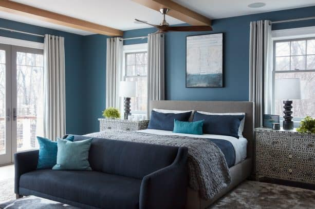 beach-style master bedroom with the cerulean wall, ash-gray carpeted, and charcoal and fossil bed