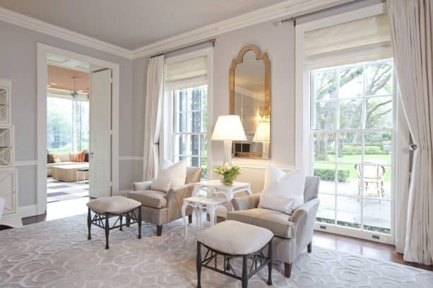 luxurious living room in pale gray wall and gold trim mirror as decoration