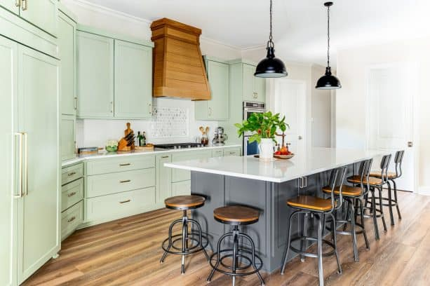 open kitchen with two islands and pretty sage green cabinets