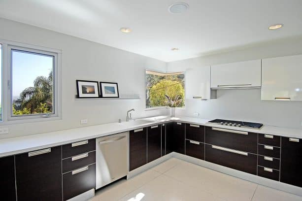white flat-panel kitchen cabinets and black stainless steel appliances? why not?