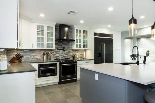 white shaker kitchen cabinet with black appliances and gray backsplash