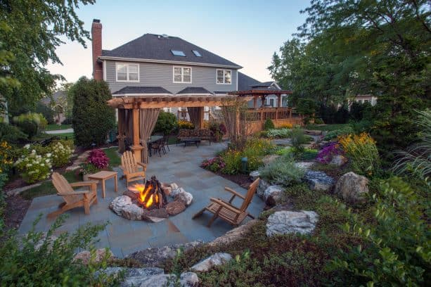a traditional backyard stone paver patio with a pergola and a fire pit