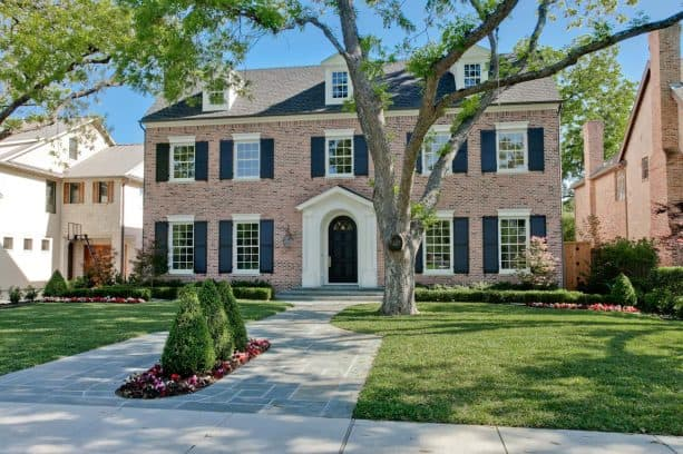 large timeless house with antique brick and matched door shutters