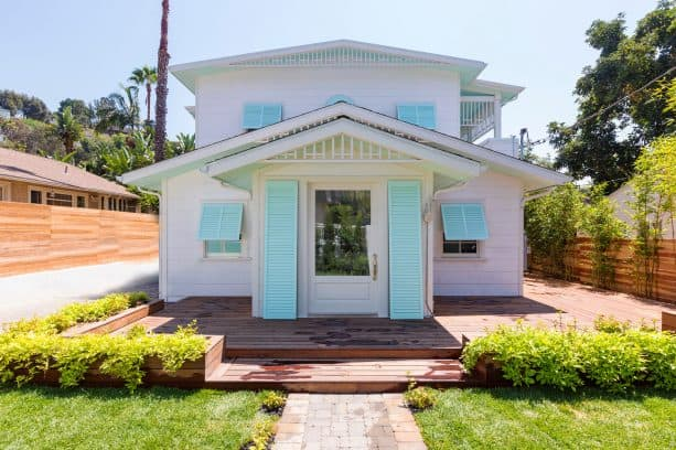 mid-size beach house in white exterior with aquatic blue window & beside door shutters