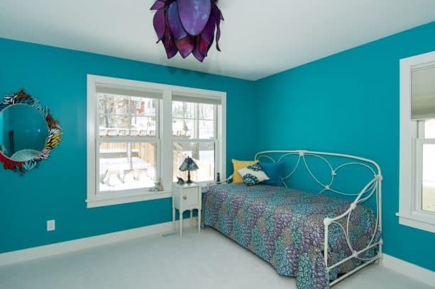 teal walls and an artistic purple lamp cover create a stunning craftsman bedroom