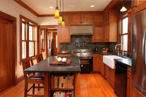 stained red cabinets paired with stainless steel appliances and cream wall paint