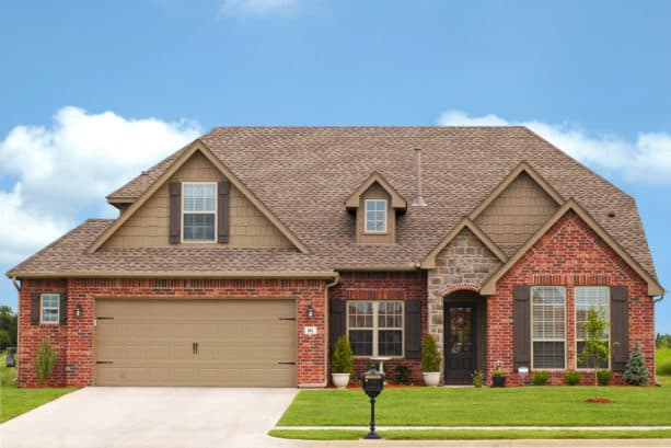 creating a cozy exterior with the combo of taupe siding and red brick wall