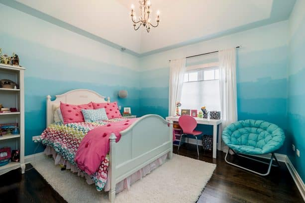 a transitional kids bedroom with ombre blue walls and white curtains