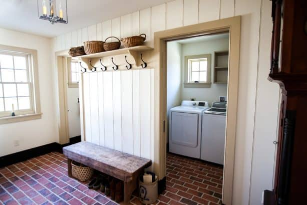 a farmhouse laundry room with brick tile as the floor material
