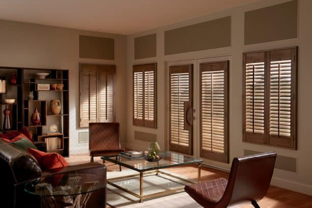 brown hardwood plantation shutters on French doors and windows