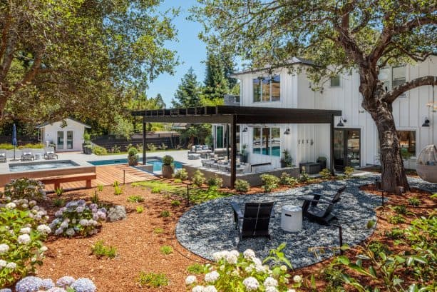 transitional backyard landscape with brown mulch and rock patio