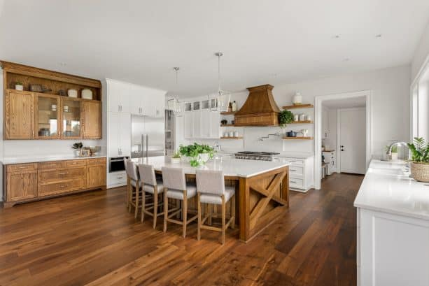 hickory cabinets and dark wood floor in a white-dominated kitchen