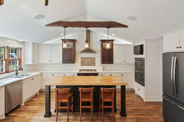 a farmhouse kitchen with slate appliances, white cabinets, and wood accents