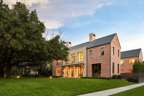 a transitional orange brick house with simple yet stunning charcoal metal roof
