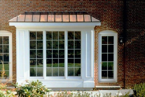 a white box bay window with metal roof in a brick house design