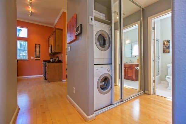 a unique laundry closet with mirrored sliding doors