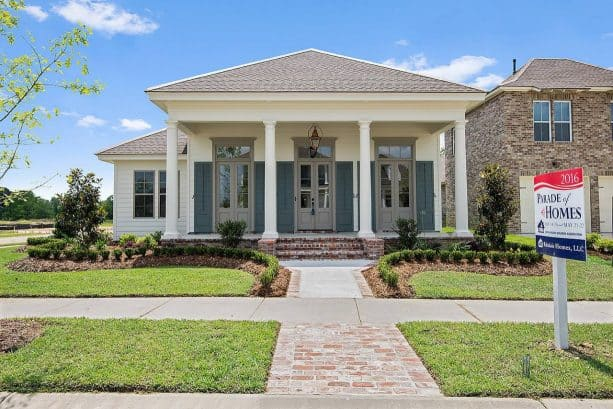 coordinating grey windowed-doors and trim in a traditional white home exterior design