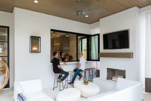 trendy black pass through window between a kitchen and a semi-outdoor living area