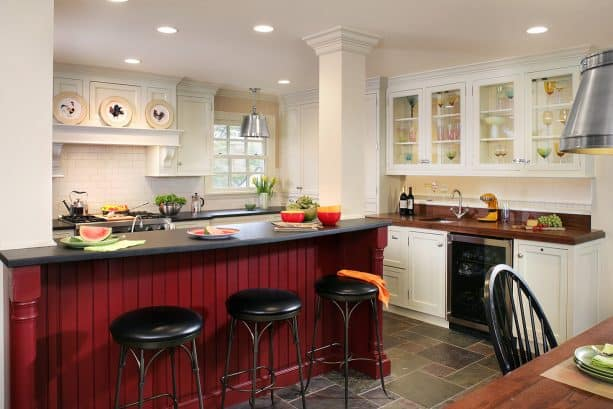 a traditional warm white kitchen with boldly elegant red island with black countertop