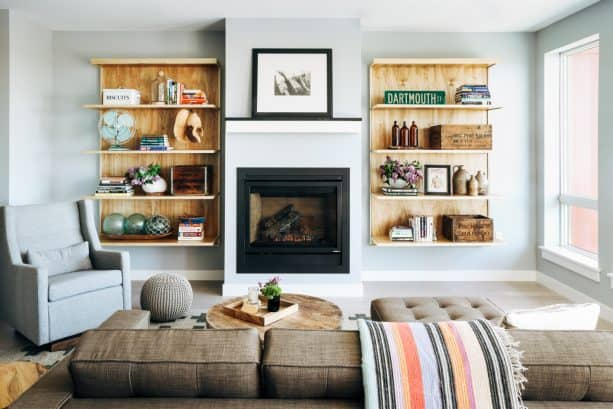 a simple, black, standard fireplace paired with a two medium-tone bookshelves in floating style