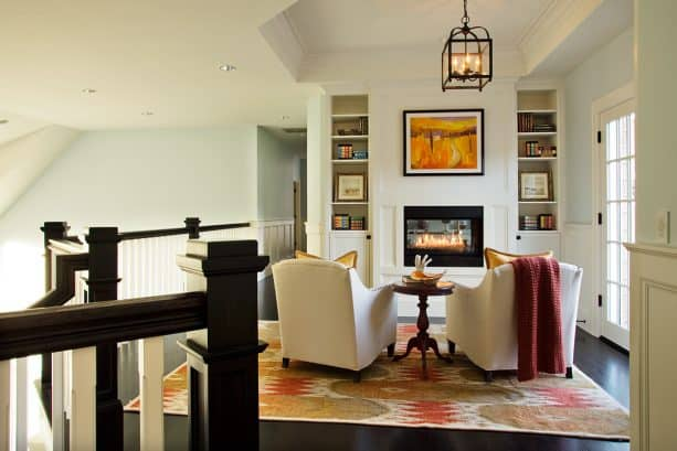 custom fireplace and bookshelves built in a small space near the staircase