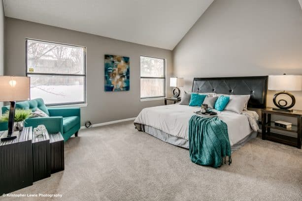 a large transitional master bedroom with gray carpet and teal sofa
