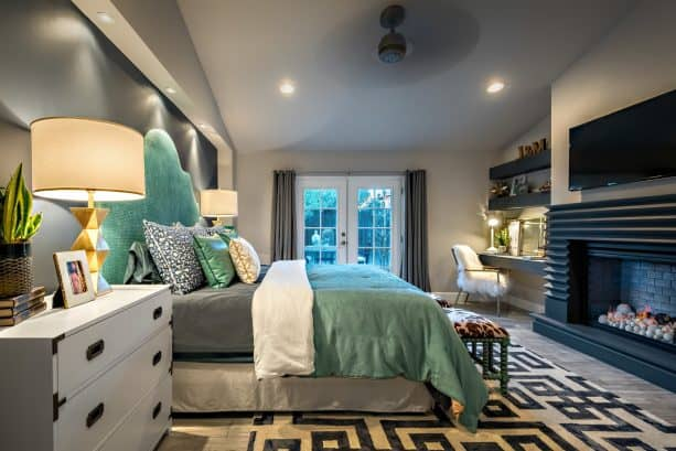 a mid-sized transitional master bedroom painted in the gray wall and ash-gray floor, teal and fog bed, and charcoal fireplace