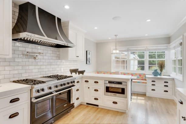 milky white cabinets with transitional u-shaped kitchen and black stainless-steel appliances