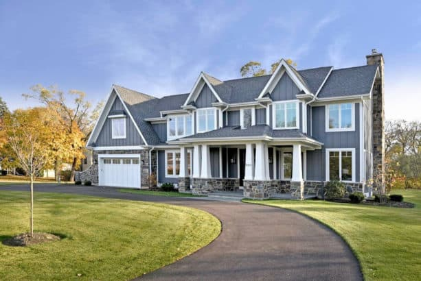 a gray craftsman exterior design with white trim and grey-color natural stone