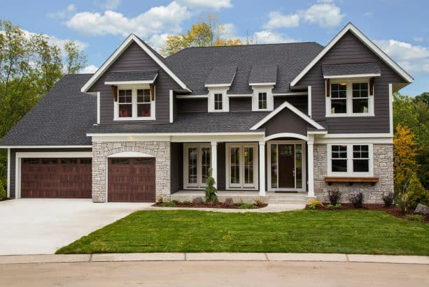 a transitional home exterior design with dark grey walls, stone walls, and white trim