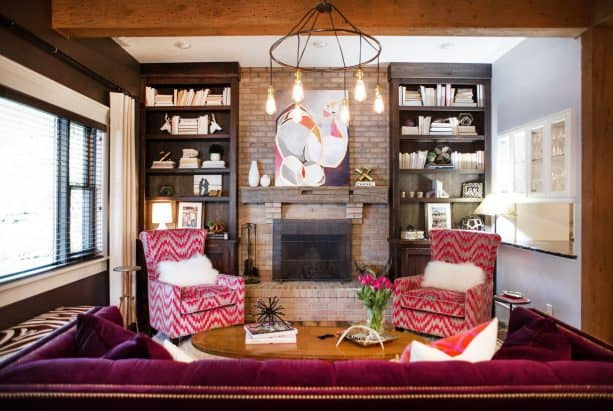 a rustic brick fireplace get a glamor enhancement because of the brown weathered wood custom bookshelves in both sides