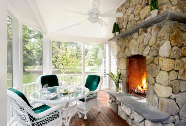 the pairing between white-themed screened porch and yellow stone fireplace
