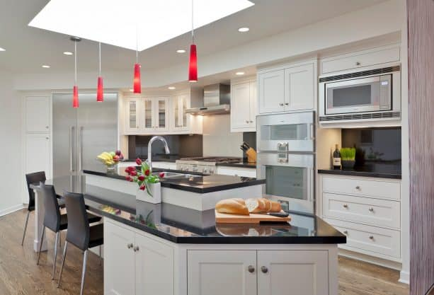 a black and white contemporary kitchen with elegant red pendant lights above the island