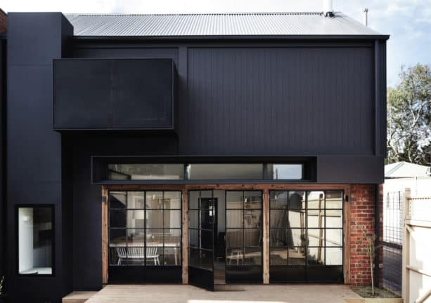 the combination of black siding, red brick, and glass doors