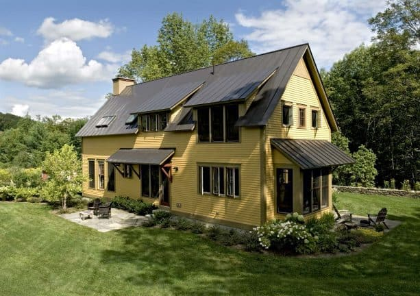 cottage wood exterior with a combination of yellow siding and a bronze metal roof