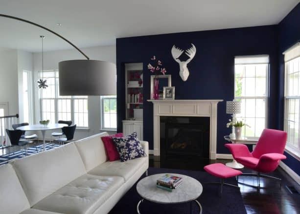 living room with navy blue wall and fuchsia pink chair