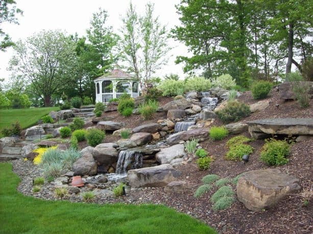 creating a waterfall on a slope with rocks and mulch