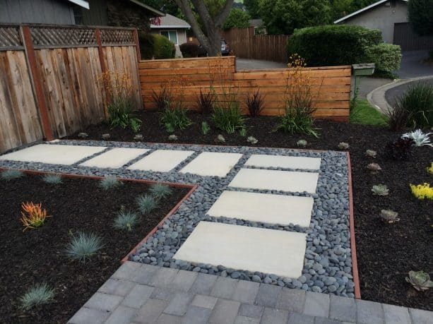 the use of black mulch and river rocks in a modern pathway landscape