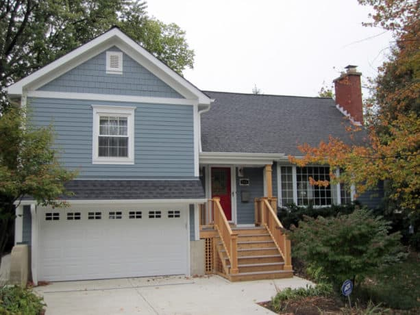 a slate blue house with white trim and currant red front door