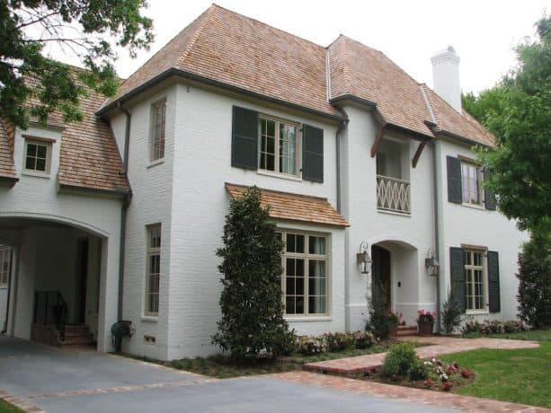 white painted brick and brown roof shingles combination in a traditional home exterior