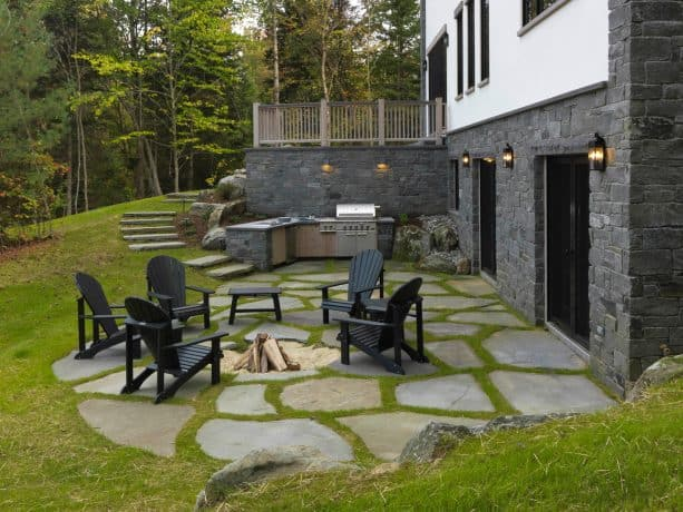 a roofless traditional walkout basement patio with black outdoor chairs, fire pit, and a grilling station