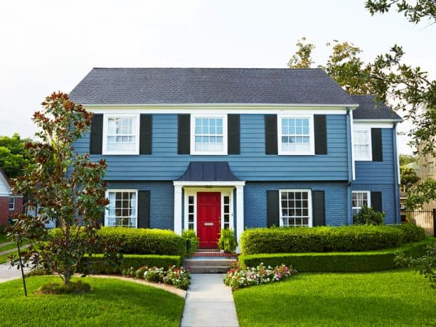 a classic and timeless exterior look with stone blue wall and berry red front door