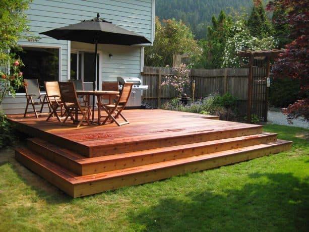 a light grey house with gorgeous orange cedar deck