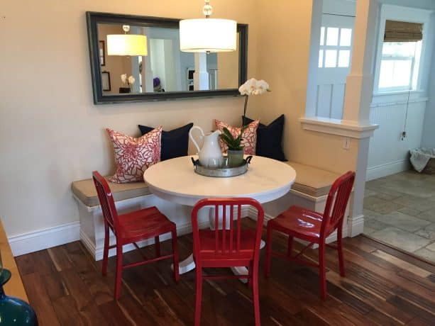 a white breakfast nook with black and red accents