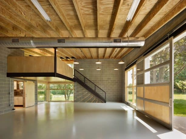 three-car stylish garage with a mezzanine apartment and a metal insulated glass door
