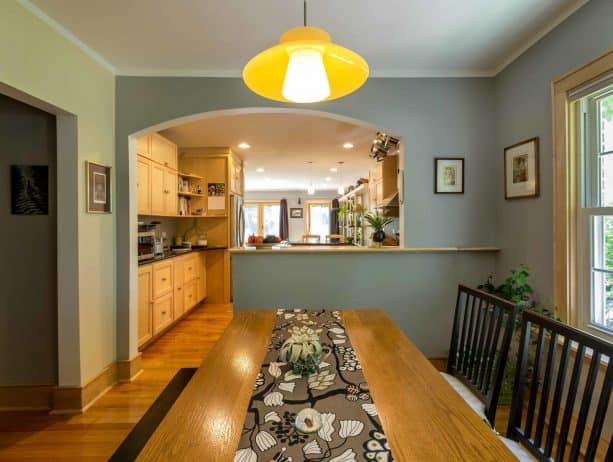 a half wall with top in an eclectic dining room and kitchen