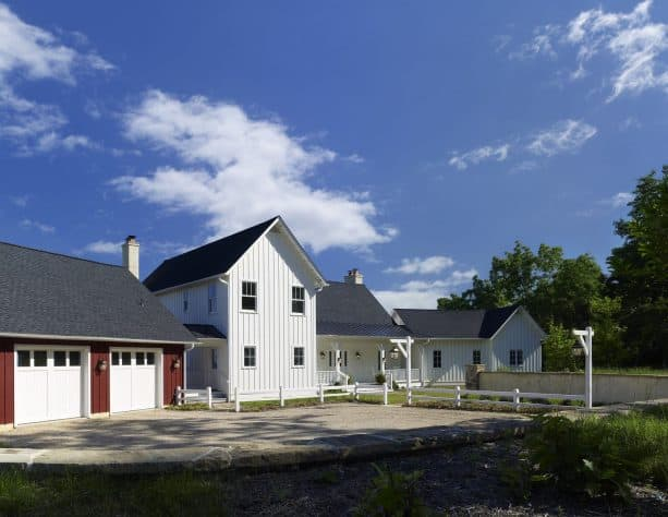 an elegant farmhouse exterior with White Dove OC-17 and Cottage Red PM-15 paint color combination
