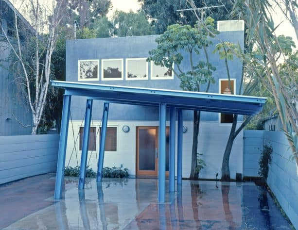 a unique blue steel carport with coordinating color with the exterior color scheme