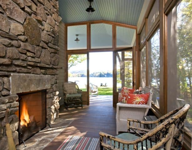a narrow screened porch with natural stone fireplace